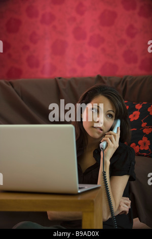 Woman using landline phone and laptop computer in living room, biting lip - Stock Photo