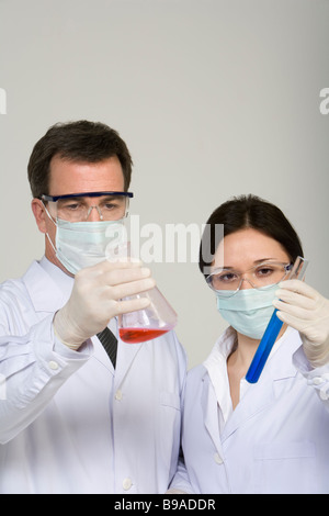 Scientists examining liquids in beakers - Stock Photo