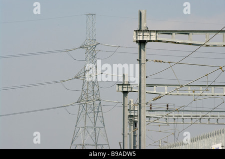 Suspended Overhead Power Lines with an Electricity Pylon In The Background - Stock Photo