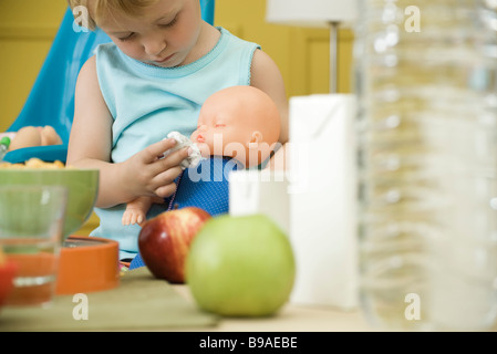 Toddler girl playing with baby doll at table - Stock Photo