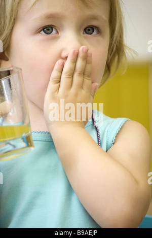 Little girl holding glass of juice, covering mouth with one hand - Stock Photo