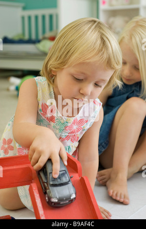 Little girl playing with toy car, sister in background - Stock Photo