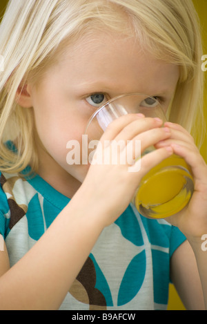 Little girl drinking glass of juice, close-up - Stock Photo
