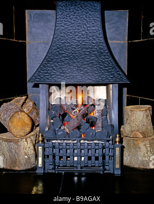 Fireplace cast iron . Real effect gas wood and coal burning cast iron fireplace with slate tile surround and freshly - Stock Photo