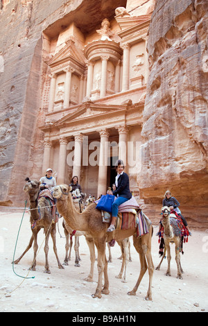 tourists riding camels  in front of the Treasury, Petra Jordan - Stock Photo
