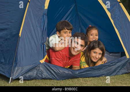 Family lying in a tent and smiling - Stock Photo