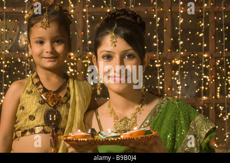 Woman with her daughter holding a traditional Diwali thali - Stock Photo