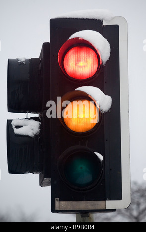 A British traffic light changes from red to amber as snow settles on it in London, United Kingdom. - Stock Photo