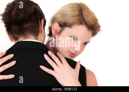 Portrait of young couple in embrace dancing, studio shot - Stock Photo