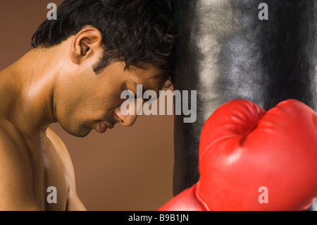 Boxer with his head leaning on a punching bag - Stock Photo