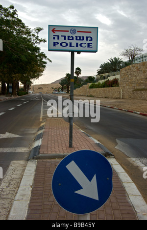 Sign in Hebrew and English on centre median of waterside drive indicating location of police station - Stock Photo