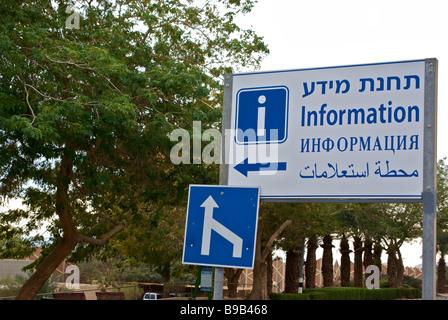 Information sign written in English Russian Hebrew and Arabic in resort town of Ein Bokek on Dead Sea - Stock Photo