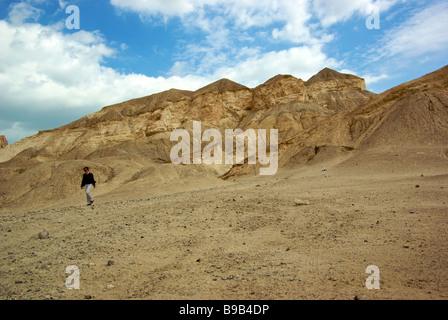 Woman walking down hiking trail from barren ridge on the desolate Judean Desert a former ocean floor near summit - Stock Photo
