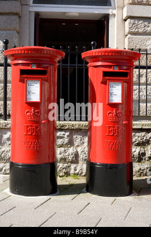 Two colourful red British postboxes outside Falmouth Post Office. - Stock Photo
