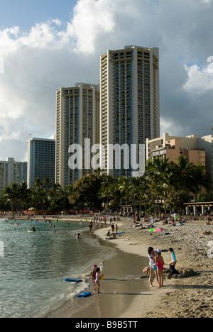 Families enjoy the sand, Waikiki Beach, Honolulu, Oahu, Hawaii. - Stock Photo