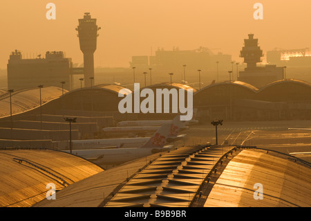 Smog shrouds Hong Kong Chek Lap Kok Airport at sunset. - Stock Photo