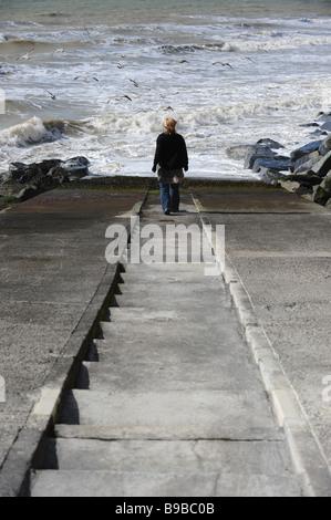 A woman alone walks towards the sea in Brighton
