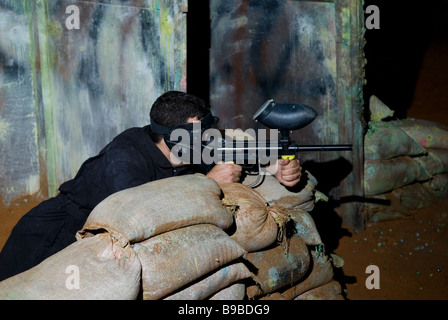 Young man playing paintball - Stock Photo