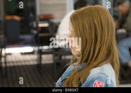 Young woman sitting outdoors, profile - Stock Photo