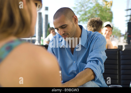 People sitting at sidewalk cafe, focus on man in middle ground - Stock Photo