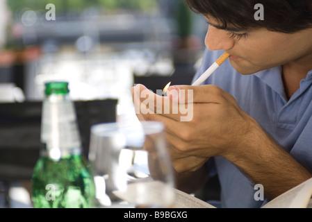 Young man lighting cigarette - Stock Photo