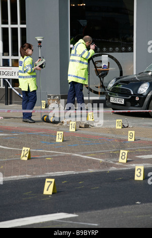Forensic police take evidence after a road traffic accident leaves a car on the pavement, on Clapham High Street, - Stock Photo
