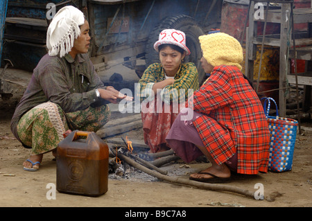 Burmese day labourer sitting on small fire at the ferry station of Mandalay Myanmar - Stock Photo