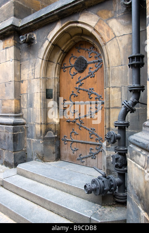 Old gothic door of St. Vitus Cathedral with metal pipe on foreground. - Stock Photo