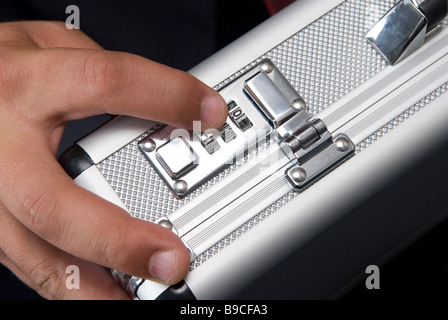 Business man unlocking a combination lock a of a briefcase - Stock Photo