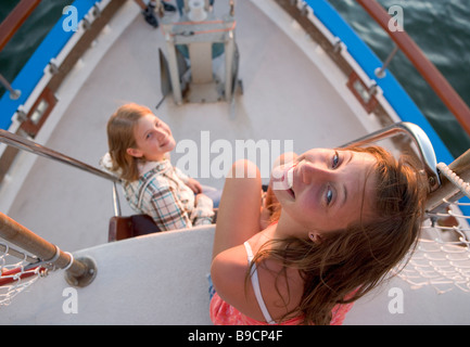 Two teen-aged girls near the bow of a tour boat at sunset - Stock Photo