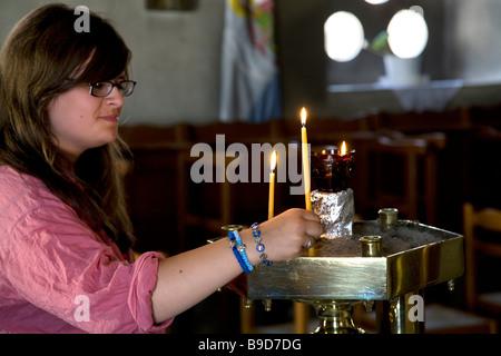 Young Woman Lighting Candle in Church of Metamorphis Vathy Samos Greece - Stock Photo