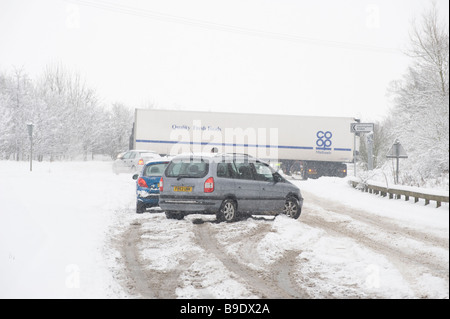 A jackknifed lorry holding up traffic on a snow covered road on a winters day in England - Stock Photo