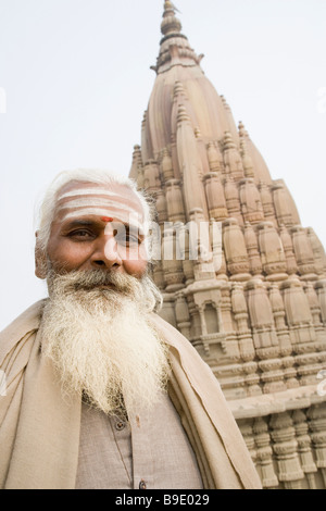 Portrait of a sadhu with a temple in the background, Scindia Ghat, Ganges River, Varanasi, Uttar Pradesh, India - Stock Photo