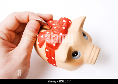 Saving money concept coin inserted in cute piggy bank - Stock Photo