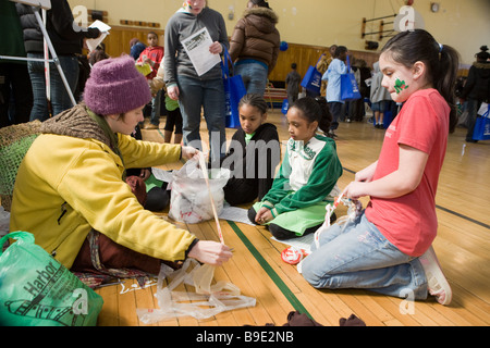 Woman teaching kids how to crochet using recyclable plastic at a Green Fair in Syracuse New York - Stock Photo