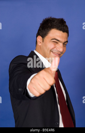 Business man winking and thumbs up - Stock Photo