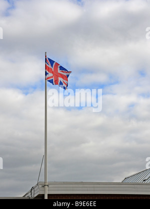 The Union Jack flag flying from a building rooftop. - Stock Photo