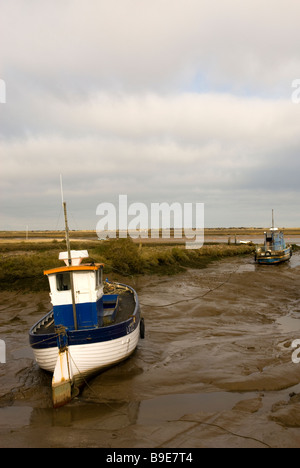 Fishing boats moored on the saltings salt marshes at Brancaster Staithe Norfolk England - Stock Photo