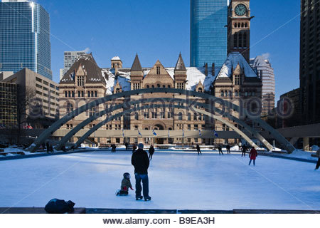 Skating in Nathan Phillips Square with old city hall recycled as a courthouse in background in Toronto Ontario Canada - Stock Photo