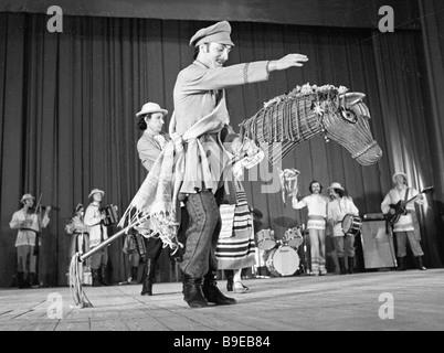 A Khoroshki Belarussian folk dance company soloist rides a hobbyhorse on stage - Stock Photo