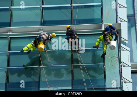 Window cleaners abseiling down a modern office block in Birmingham West Midlands England UK - Stock Photo
