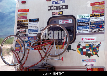 Bicycle and funny bumper sticker signs mounted on back of rv recreational vehicle camper stock