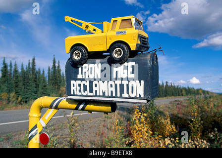 Iron Age Reclamation Business Company Sign on Rural Mailbox with Recycled Toy Tow Truck on Top - Stock Photo