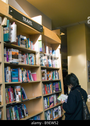 UK.Visitor reading a book in Travel section at Borders Bookshop,London,England.Photo by Julio Etchart - Stock Photo