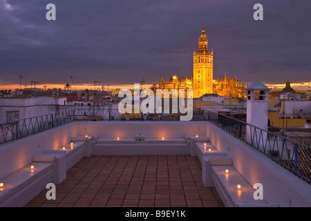 La Giralda and Sevilla Cathedral seen from the terrace at the Banos Arabes Arab Baths Aire de Sevilla at dusk Santa - Stock Photo