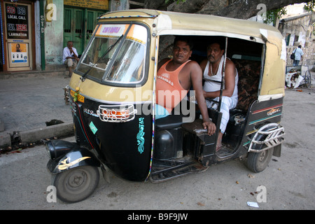 Indian Driver and Friend relaxing in their Tuc-tuc, Calcutta Street - Stock Photo