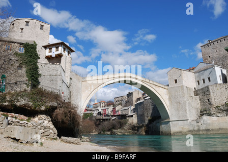 Old Bridge in Mostar Bosnia and Herzegovina with the old town and blue sky in background. - Stock Photo