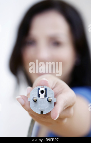 Close-up of woman's hand showing electric plug - Stock Photo