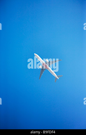 Emirates Airlines Boeing 777-300ER in flight against a clear deep blue sky - Stock Photo