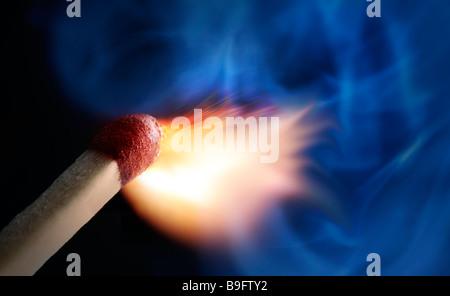 Close up of burning Match against black background - Stock Photo